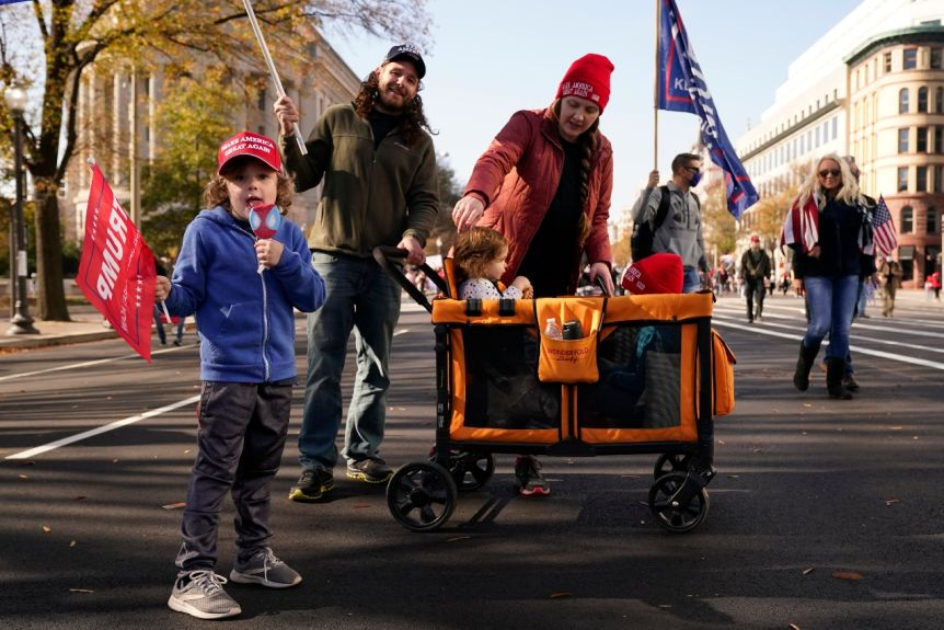 A family stands on the street carrying trumpets and children in a pram