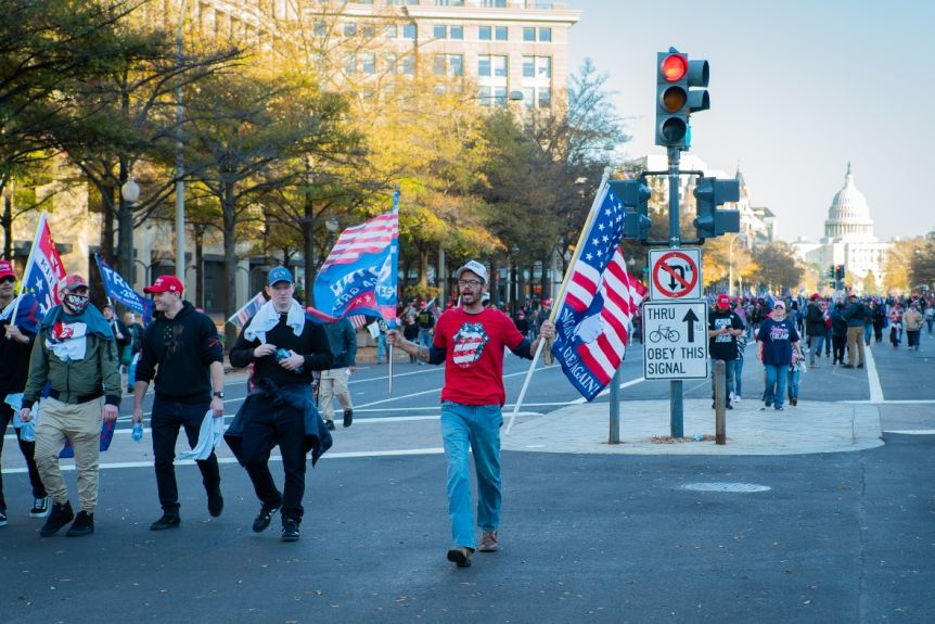 Men carrying Trump flags take out in front of groups of people in Washington, DC