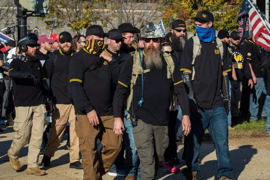 Men in black and yellow polo shirts and hats walk outside in a group