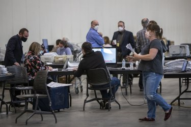 Election officials, polling observers, and contestants monitor the absentee vote count in Grand Rapids, Michigan.