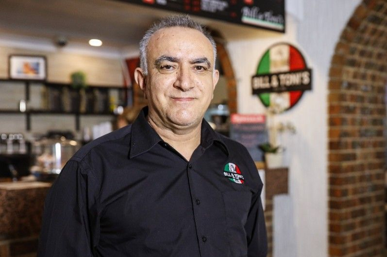 A smiling man in an Italian restaurant.