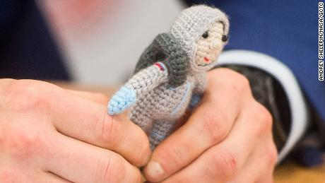 A member of the Expedition 64 crew member Sergey Kod Svershkov carries a knit astronaut named Yuri, who was made by his wife Olga.