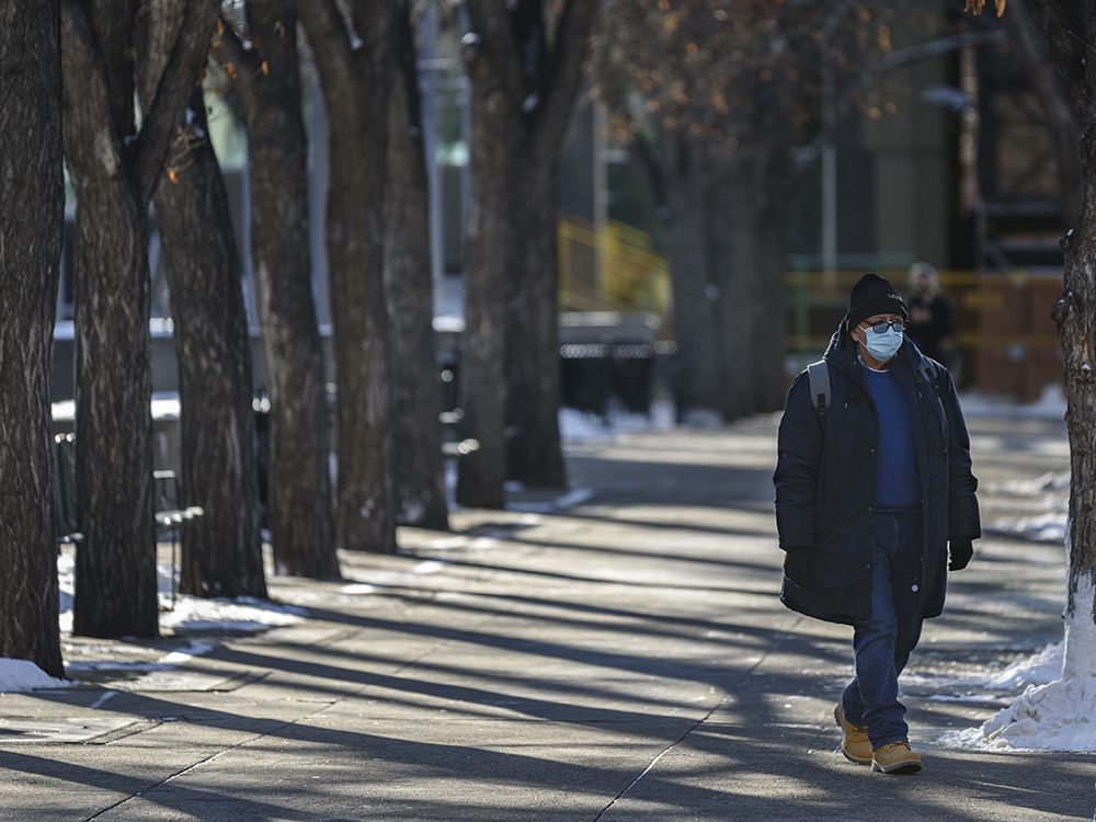 A masked pedestrian walks in downtown Calgary on Friday, Nov. 20, 2020. For the second day in a row, COVID-19 cases hit record highs in Alberta on Friday.