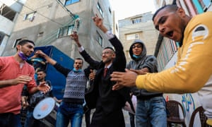 Palestinian groom Muhammad Ahmad Ashour dances with his male relatives and friends while waiting for his bride during his wedding amid the COVID-19 pandemic in Gaza City.