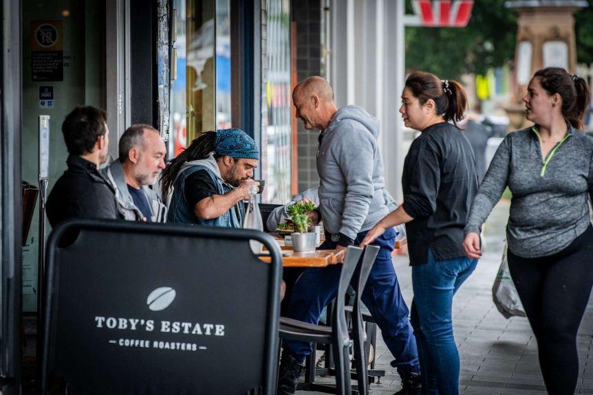 Shepherds sit outside a busy Sydney cafe.