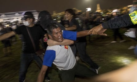 Pro-democracy protesters help transport an injured man