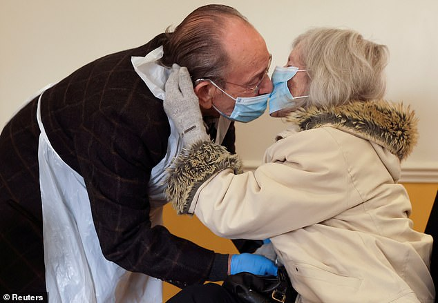 Bob Underhill, 84, and his wife Patricia, 82, who both suffer from Alzheimer's, kiss through a face mask as they are allowed to visit with physical contact for the first time at Chiswick Nursing Center in England last week.