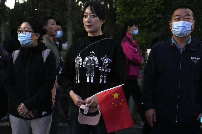 A spectator wearing a space-themed T-shirt and holding the Chinese flag waits for Chinese astronauts to arrive to prepare for takeoff at the Jiuquan Satellite Launch Center in Jiuquan, northwest China, Thursday, June 17, 2021. China plans Thursday to launch.  Three astronauts aboard the Shenzhou-12 spacecraft will be the first crew members to live on China's new space station orbiting Tianhe, or Heavenly Harmony.  (AP Photo/Ng Han Guan)