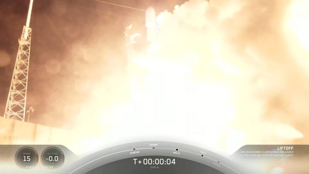 A SpaceX rocket launches a Sirius XM digital radio satellite, landing the sea at night