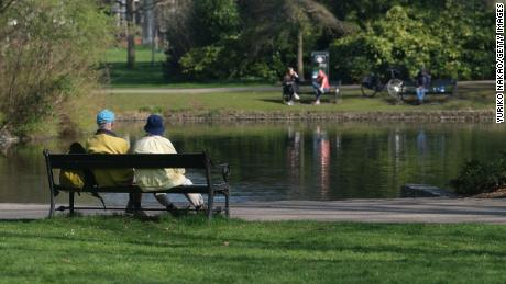 Finally, a couple sit on a bench in front of a pond at Wilhelminapark in Utrecht, Netherlands.